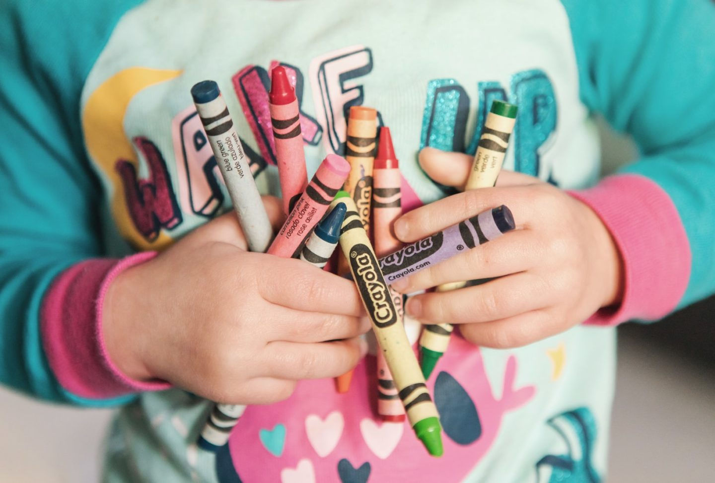 child holding crayons