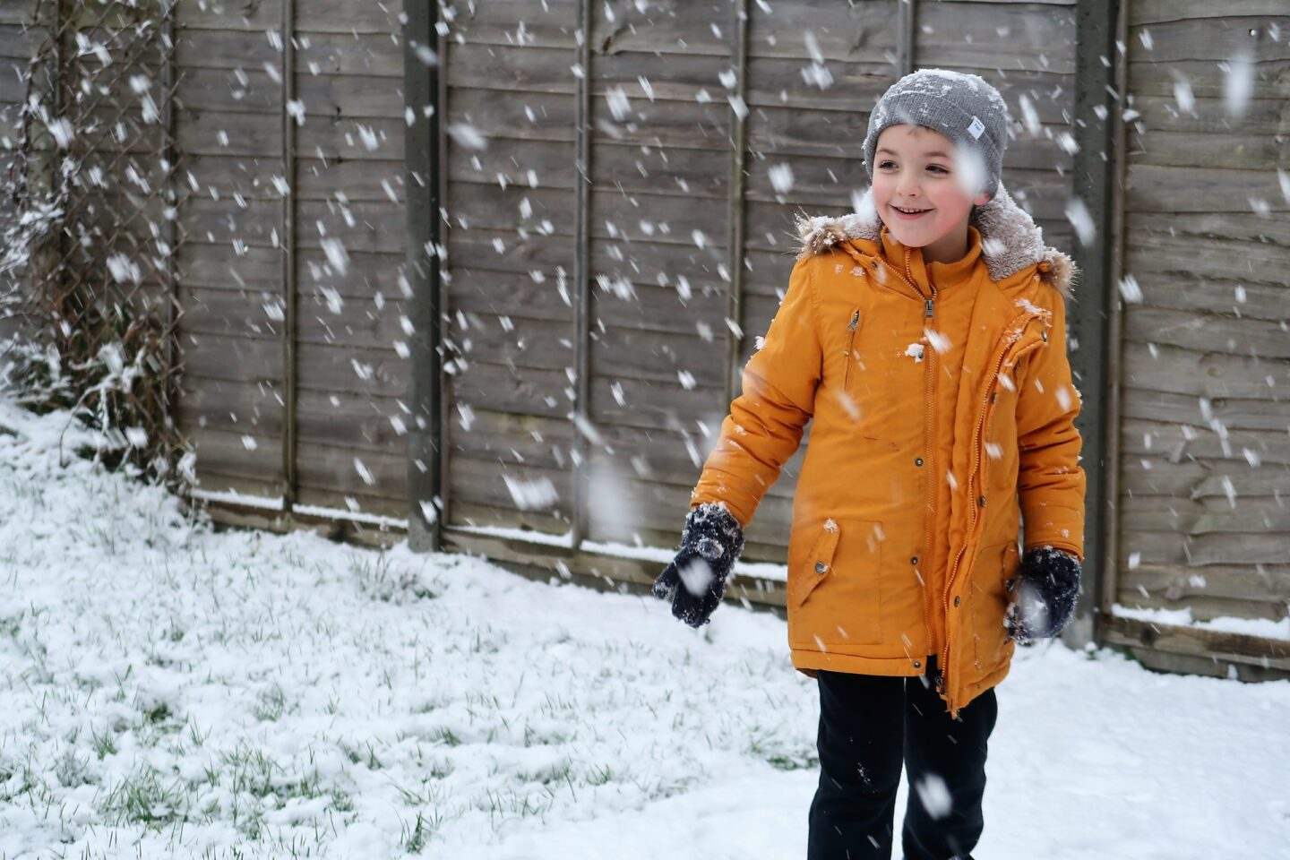 Boy in the snow in a yellow coat